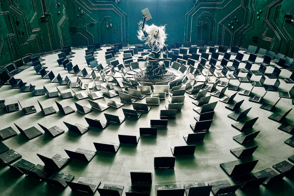 Photo #1 in the series: a cyborg model sits among a vortex of discarded laptops.
